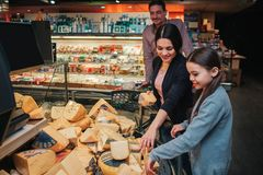 Young parents and daughter in grocery store. Mother help daughter to pick up cheese. Father stand behind and look at it stock images