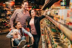 Young parents and daughter in grocery store. They pick up conservation together. Girl sit in grocery trolley woth bear royalty free stock image