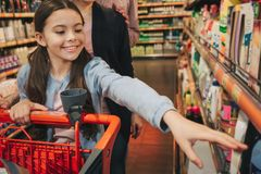 Young parents and daughter in grocery store. Small girl reach out to shelf and smile. Parents stand behind. Girl carry stock image