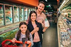 Young parents and daughter in grocery store. They stand between product shelfs and pose on camera. Girl hold trolley stock images