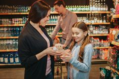 Young parents and daughter in grocery store. Woman and child hold water bottle together. Father stand behind with stock photography