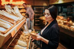 Young parents and daughter in grocery store. Woman stand in front and hold bread in hands. She look at it seriously royalty free stock images