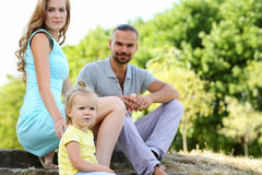 Young parents with daughter on picnic outdoor at beautiful sunny Stock Photo