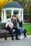 Young parents with daughter sitting on bench backdrop of mirador Stock Photo