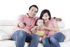 Young parents and daughter watching TV Stock Image