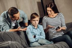 Young parents explaining son about drawbacks of binge-playing. Clear explanation. Strict young parents telling their son about the drawbacks of binge-playing on stock image