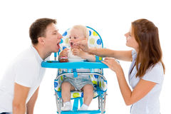 Young parents feed  baby. Young parents feed  baby on a white background. Happy family Royalty Free Stock Image