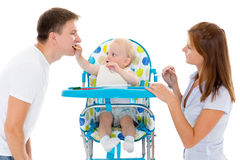 Young parents feed  baby. Young parents feed  baby on a white background. Happy family Stock Photography