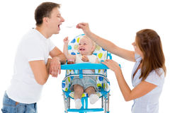 Young parents feed  baby. Young parents feed  baby on a white background. Happy family Stock Photos