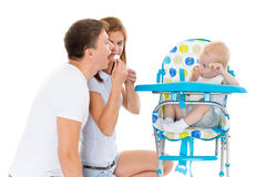 Young parents feed  baby. Young parents feed  baby on a white background. Happy family Royalty Free Stock Photography