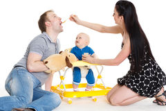 Young parents feed  baby. Royalty Free Stock Images