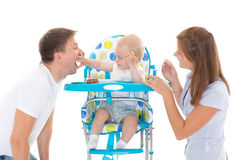 Young parents feed  baby. Young parents feed  baby on a white background. Happy family Stock Image