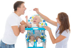 Young parents feed  baby. Young parents feed  baby on a white background. Happy family Stock Images
