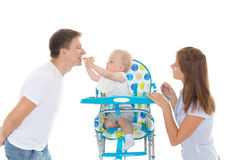 Young parents feed  baby. Young parents feed  baby on a white background. Happy family Stock Photo