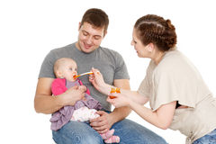 Young parents feed  baby. Royalty Free Stock Photography