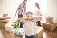 Young parents are fighting with each other and arguing. They are mad on each other. Their daughter are not happy because. Of that. She has closed her ears with Stock Photography