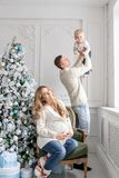 Young parents fool around and play with little son. Happy family having fun at home. Christmas morning in bright living stock photos