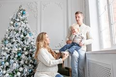 Young parents fool around and play with little son. Happy family having fun at home. Christmas morning in bright living stock photo