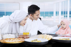 Young parents and girl having meal together Royalty Free Stock Photography