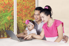 Young parents and girl looking at laptop Stock Photo