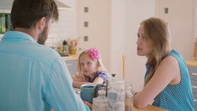 Young parents having a conversation at the kitchen table while their daughter is colouring. Slow mo stock video footage