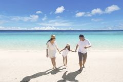Young parents with daughter on the beach Stock Photos
