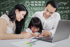 Young parents help their kid studying Stock Images