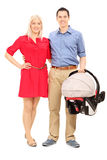Young parents holding a baby stroller Stock Images