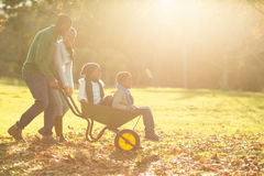 Young parents holding their children in a wheelbarrow Royalty Free Stock Photography