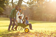 Young parents holding their children in a wheelbarrow Stock Photos