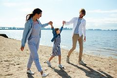 Walk by coastline. Young parents holding their happy daughter by hands while walking down sandy beach by coastline Stock Photo