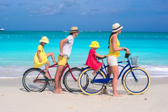 Young parents and kids riding bicycles on a tropical white sand beach Stock Images