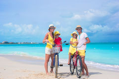 Young parents and kids riding bicycles on a tropical white sand beach Royalty Free Stock Photos