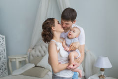 Young parents kiss each other and their little baby looks at their Stock Photography