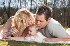 Young parents are kissing the baby Royalty Free Stock Image