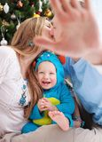 Young parents while kissing and baby son. Young parents cover camera with hand while kissing, baby son dressed in little monster costume laughing, Christmas time stock photography