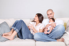 Young parents with little baby at home. Sitting on cozy divan, enjoying family, loving couple with newborn daughter, positivity and fun concept Royalty Free Stock Photo