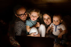 Young parents with little children and laptop at night. Young parents at home at night with their little children watching something on laptop Stock Photos