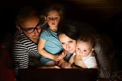 Young parents with little children and laptop at night. Young parents at home at night with their little children watching something on laptop Royalty Free Stock Images