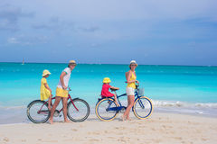 Young parents and little girls with bikes on a tropical white sandy beach Royalty Free Stock Images