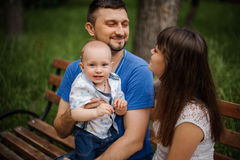 Young parents and little son in the park happy family sitting on bench Stock Image