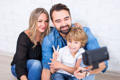 Young parents and little son taking photo with smart phone on se. Happy young parents and little son taking photo with smart phone on selfie stick Royalty Free Stock Image