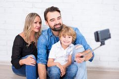 Young parents and little son taking selfie photo. With smart phone Royalty Free Stock Images