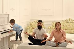 Young parents meditating, while their little son playing piano, annoying parents. Couple do yoga exercises in bed. Kid. Annoyed parents with noise. Mom and dad royalty free stock photo