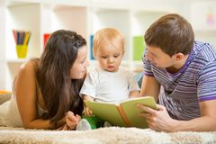 Young parents mom and dad reading children book to stock photography