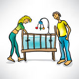 Young parents next to baby's crib Royalty Free Stock Images