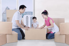 Young parents packing cardboard with their daughter Royalty Free Stock Photos