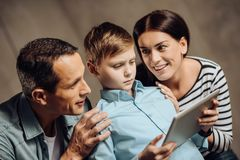 Young parents persuading son to stop binge-playing. Persuasive strategies. Gentle young parents surrounding their pre-teen son and touching him tenderly while stock photo