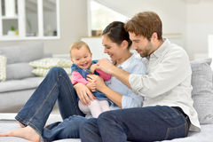 Young parents playing with baby girl on sofa Royalty Free Stock Photography
