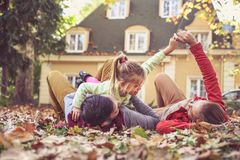 Young parents playing with daughter at front of backyard. Stock Images